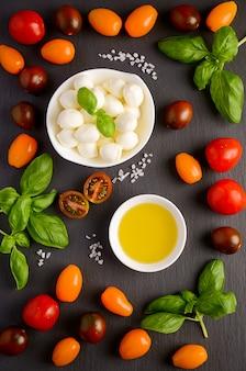 Ingredienti alimentari italiani - mozzarella, pomodori, basilico e olio d'oliva sul nero