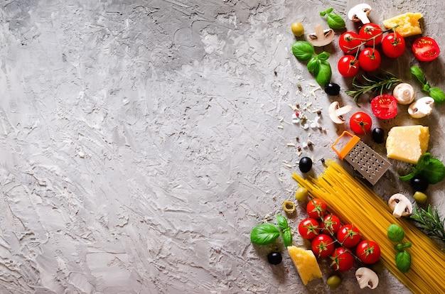 Ingredienti alimentari per pasta italiana, spaghetti su sfondo grigio cemento.