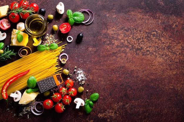 Ingredienti alimentari per pasta italiana, spaghetti su sfondo scuro marrone.