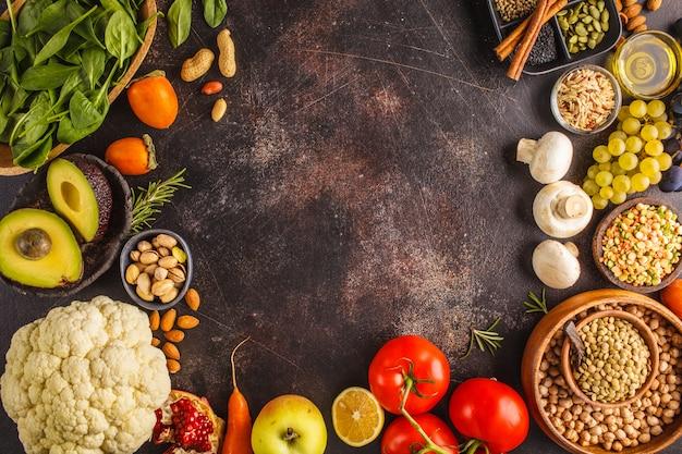 Ingredienti alimentari vegani su uno sfondo scuro. verdura, frutta, cereali, noci, fagioli vista dall'alto.