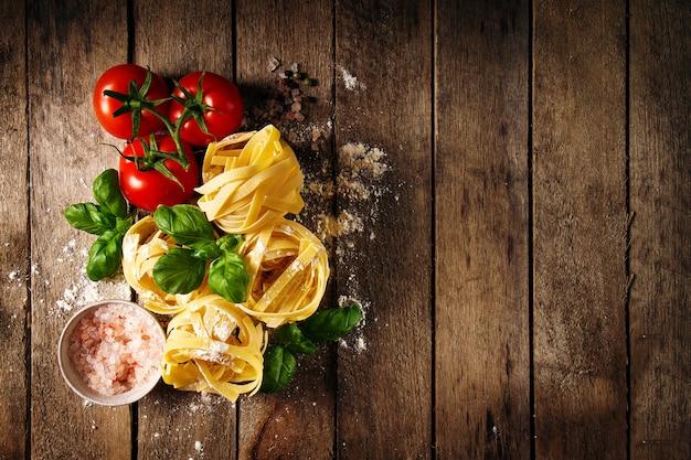 Ingredienti colorati freschi e saporiti per la cottura di pasta tagliatelle con basilico fresco e pomodori. vista dall'alto. sfondo di tavola in legno.