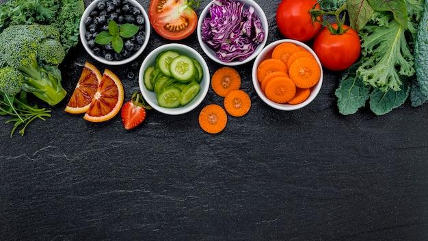 Ingredienti colorati per frullati e succhi sani su fondo di pietra scura con spazio di copia.