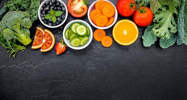 Ingredienti colorati per frullati e succhi sani su pietra scura