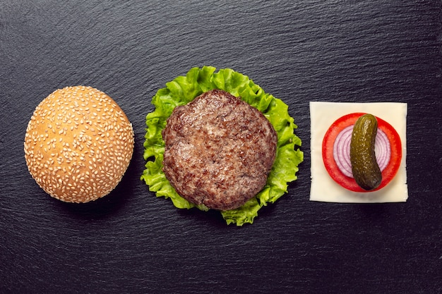 Ingredienti del buger di vista superiore su fondo nero