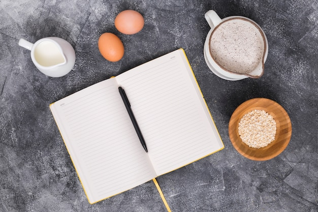 Ingredienti del pane con libro e penna su sfondo concreto