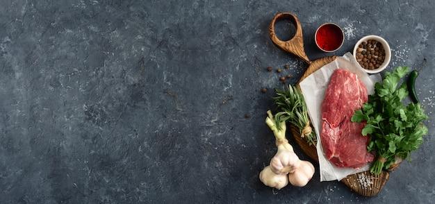 Ingredienti della carne cruda sul bordo di taglio di legno sulla pietra scura con la vista superiore del copyspace. menu del ristorante