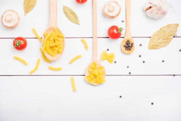Ingredienti della pasta con le spezie e le verdure sulla tavola bianca della plancia