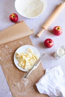 Ingredienti di cottura disposti sul tavolo, pronti per la cottura di pasticceria per la torta di mele americana. concetto di preparazione del cibo - vista dall'alto