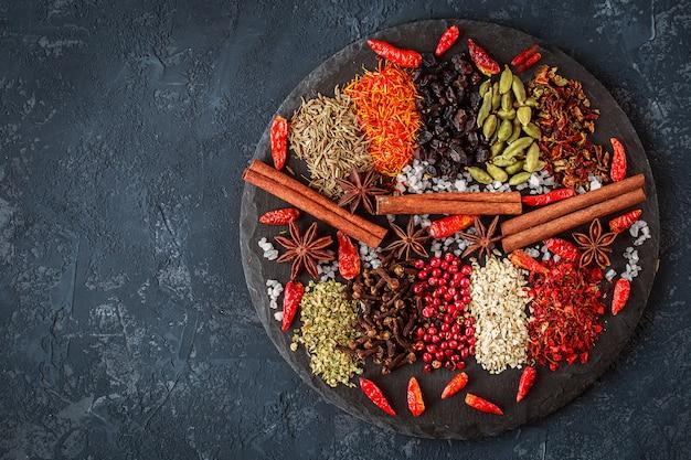 Ingredienti di erbe e spezie su ardesia su cemento scuro