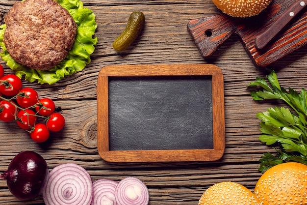 Ingredienti di hamburger piatto laici con lavagna