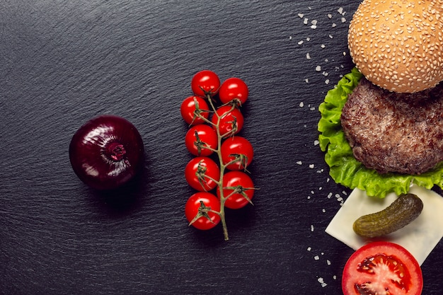 Ingredienti di hamburger piatto laici su sfondo di ardesia