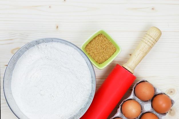 Ingredienti e strumenti di cottura per fare un panificio, farina in colpo, zucchero, uova