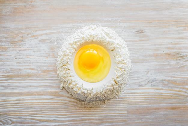 Ingredienti e strumenti per la cottura - farina, uova e bicchiere di latte sulla tavola rustica in legno. preparazione della pasta fatta in casa