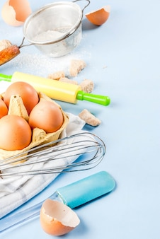 Ingredienti e utensili per cucinare uova, farina, zucchero, frusta, mattarello