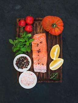 Ingredienti. filetto di salmone crudo, pomodori al limone, ciliegia e cimelio, menta fresca, spezie su tavola di legno rustico su sfondo di pietra scura