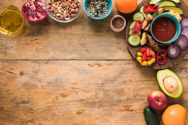 Ingredienti; frutta secca; frutta; olio e verdure a fette sul tavolo di legno