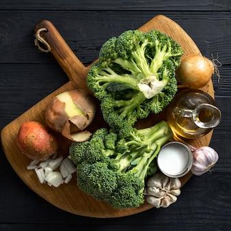 Ingredienti grezzi per la cottura della minestra crema dei broccoli su una tavola di legno