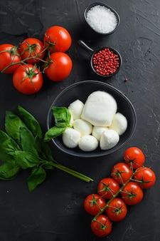 Ingredienti insalata caprese: palline di mozzarella con pomodoro e basilico