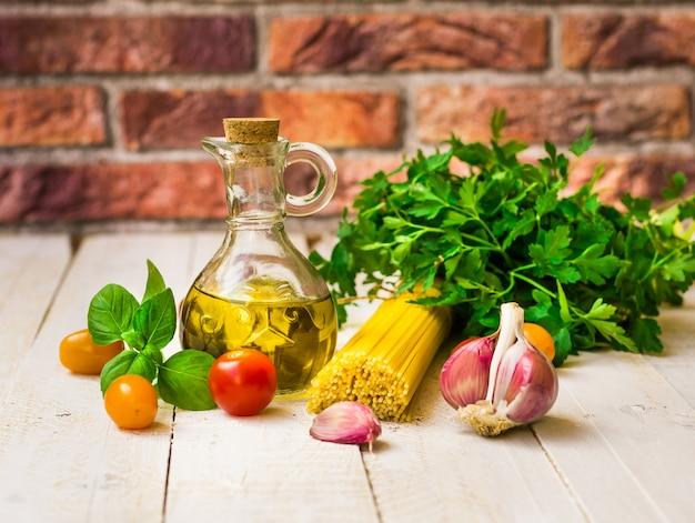 Ingredienti pasto sano italiano, spaghetti, pomodori, olio d'oliva, aglio, basilico, erbe