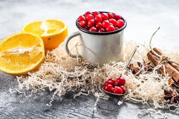 Ingredienti per biscotti da forno invernali pan di zenzero, torta di frutta, bevande mirtilli, arance, cannella, spezie cibo natalizio superficie grigia