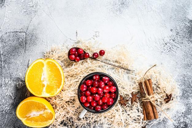 Ingredienti per biscotti da forno invernali pan di zenzero, torta di frutta, bevande mirtilli rossi, arance, cannella, spezie cibo natalizio superficie grigia
