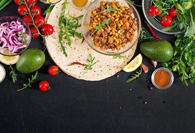 Ingredienti per burritos avvolge con carne e verdure su sfondo nero. vista dall'alto