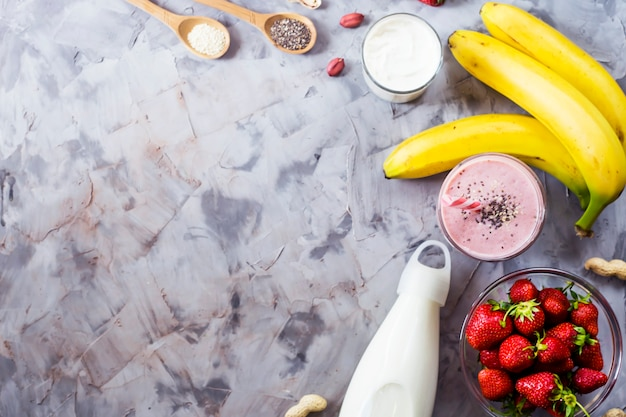 Ingredienti per cucinare frullati di fragole, banane, latte, yogurt