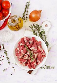 Ingredienti per cucinare i cuori di pollo con zucca e pomodori in salsa di pomodoro. il contorno è servito con riso bollito. disteso. vista dall'alto.