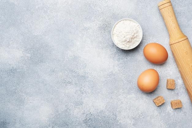Ingredienti per cuocere biscotti, cupcakes e torte. le uova crude degli alimenti farina lo zucchero su un fondo grigio con lo spazio della copia.