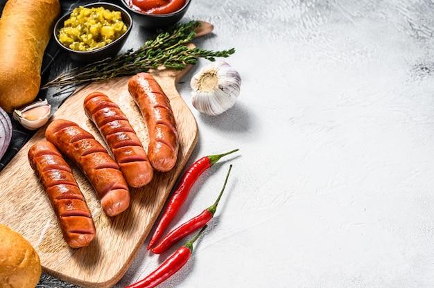 Ingredienti per diversi hot dog fatti in casa, con cipolla fritta, peperoncino, pomodori, ketchup, cetrioli e salsiccia. sfondo bianco. vista dall'alto. copia spazio