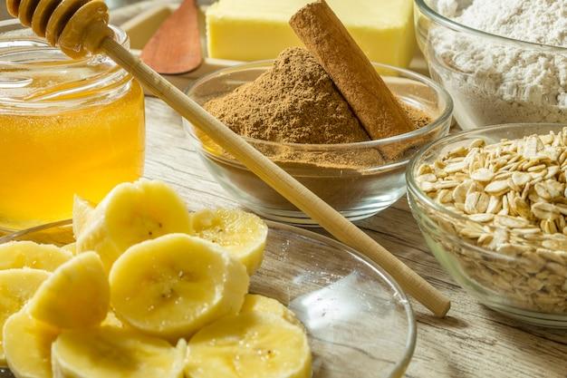 Ingredienti per fare biscotti sani. banana, farina di avena, miele, cannella e burro