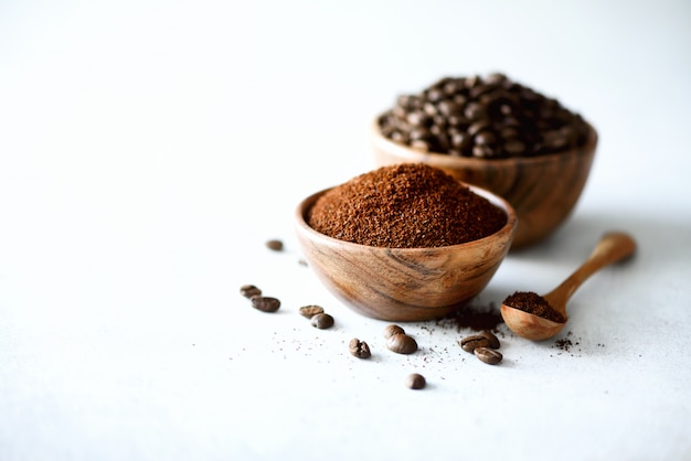 Ingredienti per fare la bevanda caffeina - chicchi di caffè, caffè macinato e solubile su cemento chiaro, copia spazio.