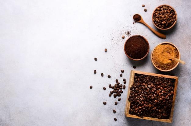Ingredienti per fare la bevanda caffeina - zucchero di cocco marrone, chicchi di caffè, caffè macinato e solubile su cemento chiaro, copia spazio, vista dall'alto.