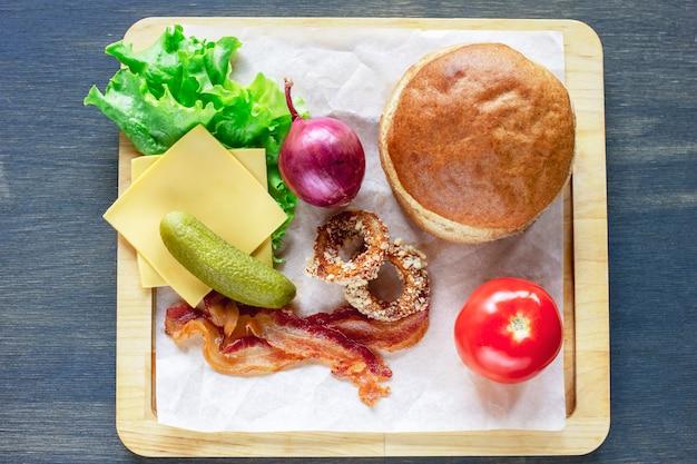 Ingredienti per hamburger, cipolla, lattuga, pomodoro, pancetta e altro