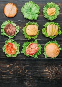 Ingredienti per hamburger. nove hamburger in diverse fasi di prontezza. vista dall'alto. superficie in legno nero