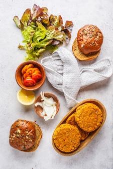 Ingredienti per hamburger vegano su sfondo bianco, vista dall'alto. hamburger di verdure, avocado, verdure e focacce.