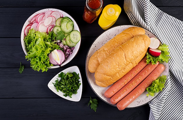 Ingredienti per hot dog con salsiccia, cetriolo, ravanello e lattuga