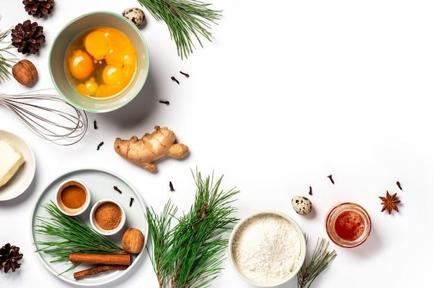 Ingredienti per i biscotti bollenti dello zenzero di natale su un fondo bianco, spazio della copia. farina, uova, zenzero, spezie, burro, rami di pino verde e coni sul tavolo, distesi.