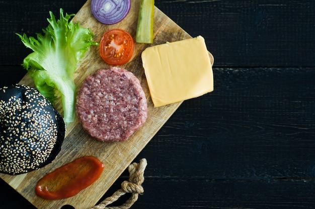 Ingredienti per l'hamburger nero sul tagliere di legno, fondo nero.