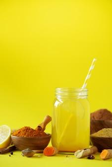 Ingredienti per la bevanda di curcuma arancione su sfondo giallo. acqua al limone con zenzero, curcuma, pepe nero. concetto di bevanda calda vegana