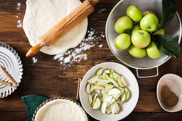 Ingredienti per la cottura delle crostate di mele casalinghe sulla vista di legno del piano d'appoggio