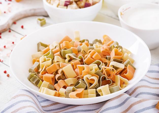 Ingredienti per la cottura di pasta cremosa con pollo e melanzane servita nel piatto fondo.
