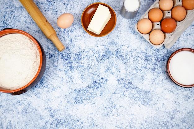 Ingredienti per la cottura: uova, farina, zucchero, burro, latte su uno sfondo di cemento azzurro, pietra o ardesia. vista dall'alto con spazio per il testo.