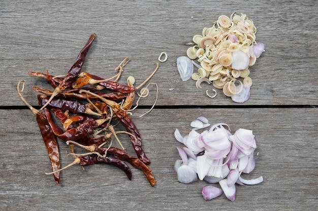 Ingredienti per la cucina tailandese nel piatto (peperoni, cipolle, citronella) su fondo di legno