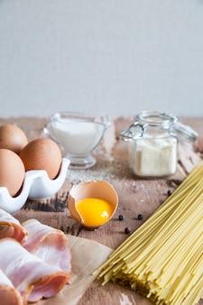 Ingredienti per la pasta alla carbonara con pancetta, formaggio, panna e tuorlo su tavola di legno