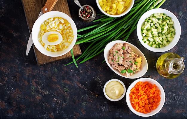 Ingredienti per la preparazione di insalata di fegato di merluzzo con uova, cetrioli, patate e carote in ciotole.