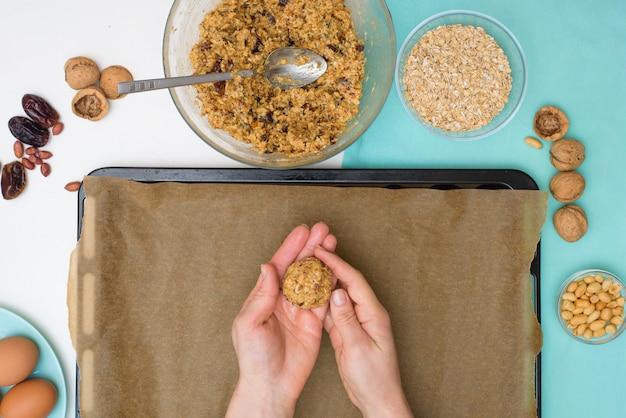 Ingredienti per la ricetta biscotti di farina d'avena fatti in casa con datteri, arachidi, scaglie di cocco, che formano un impasto rotondo per biscotti