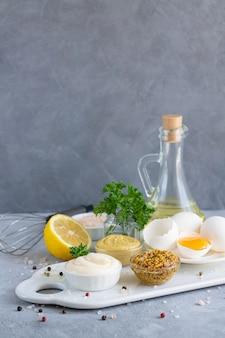 Ingredienti per la salsa maionese fatta in casa: senape, uova, olio d'oliva, limone, spezie ed erbe aromatiche su fondo di pietra