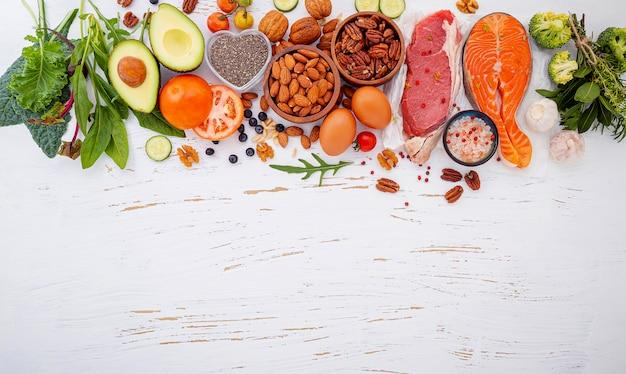 Ingredienti per la selezione di alimenti sani su fondo di legno bianco.