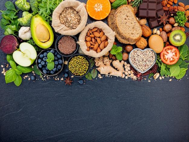 Ingredienti per la selezione di cibi sani. il concetto di cibo sano istituito su sfondo di pietra scura.